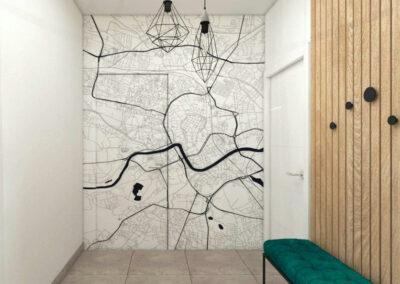 Hol z dekoracją na ścianie w postaci mapy Krakowa oraz ukrytymi drzwiami a także zielonym siedziskiem