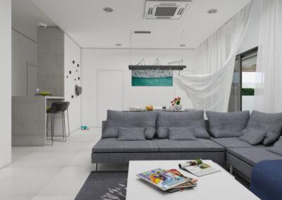 Biały salon z szarą sofą