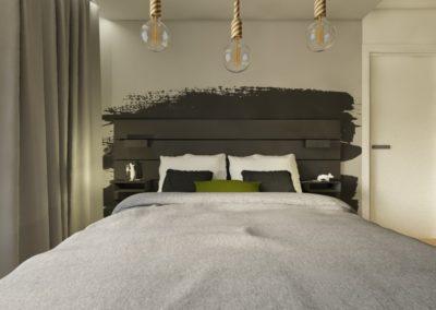 Sypialnia z zielono szarymi ścianami i grafitowym wykończeniem łóżka oraz podwieszonymi żarówkami na sznurku